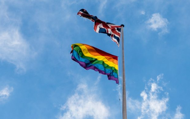 A pride flag and the Union flag flying on a flag pole above the Department for International Development