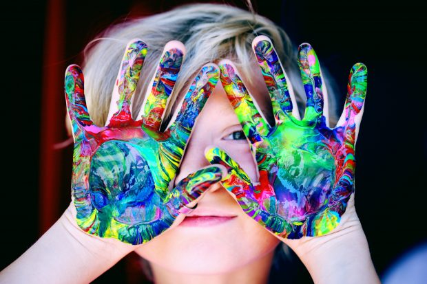 A child with a rainbow of colours painted on their hands