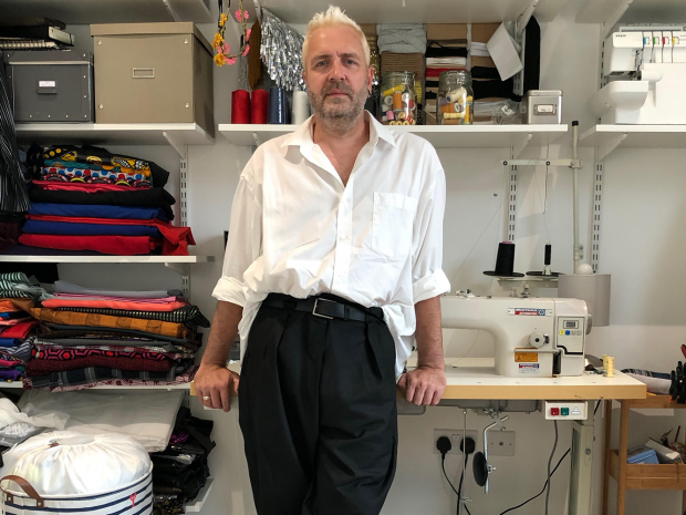 Man leaning on sewing desk