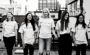 Black and white image of group of girls in front of cityscape.